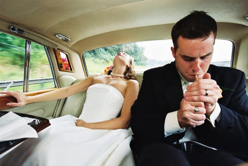 Bride and groom in limo smoking