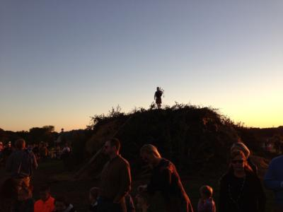Bagpiper atop the unlit brush pile